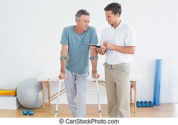 Therapeut diskutiert Berichte mit einem behinderten Patienten
