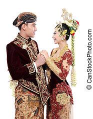 Traditionelles Java-Hochzeitspaar, Mann und Frau, halten sich wegen weißem Hintergrund isoliert