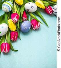 Tulpen mit farbenfrohen Ostereiern.