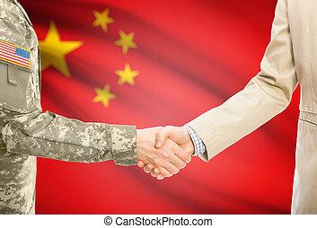 US-Militär in Uniform und Zivil Mann in Anzug schütten die Hände mit angemessener nationaler Flagge im Hintergrund - Volksrepublik China.