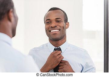 Vertraut sein Aussehen. Ein junger Afrikaner, der seine Krawatte passt, während er gegen den Spiegel steht