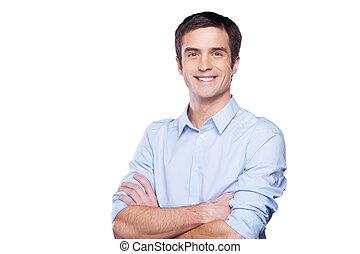 Vertrauter Geschäftsmann. Portrait eines hübschen jungen Mannes in blauem Hemd, der die Kamera ansieht und die Arme kreuzt, während er auf weiß steht