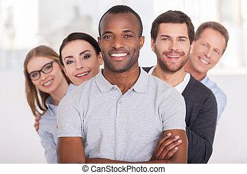 Vertrautes Geschäftsteam. Erbärmlicher junger Afrikaner, der die Arme gekreuzt und lächelt, während eine Gruppe von Leuten hinter ihm steht und sich die Kamera ansieht