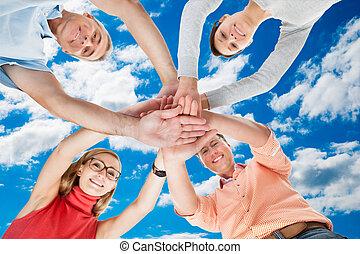 Vier zwanglose Freunde mittleren Alters, die Händchen halten.