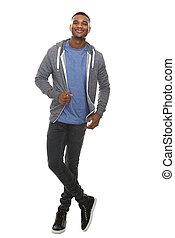 Volle Länge Porträt eines coolen jungen schwarzen Mannes lächelnd.