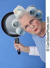 Wütende alte Dame, die droht, Pfanne zu benutzen.