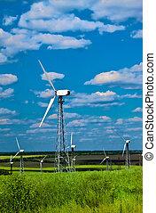 Windkraftwerk - Windturbinen gegen den blauen Himmel und grünes Gras