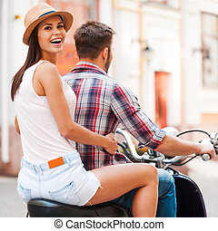 Wir untersuchen neue Orte zusammen. Rear view of beautiful young couple riding Roller together while beautiful woman looking overschul and smile