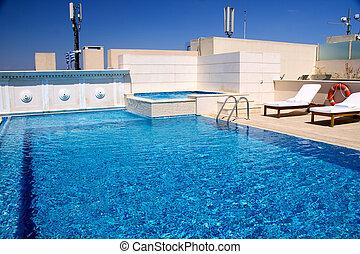 Wunderschöner Swimmingpool umgeben von Stühlen und Blumen