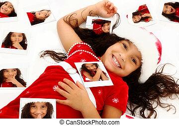 Wunderschönes hispanisches afroamerikanisches Mädchen in Santa Hut, Weihnachtskleid, umgeben von selbst polaroiden Porträts auf dem Boden.