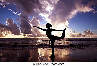Yoga-Frau am schönen Strand bei Sonnenaufgang