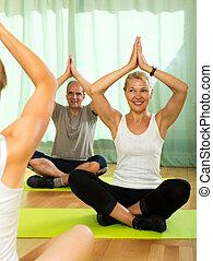 Yogalehrer mit älteren Teilnehmern.