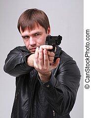 Zielen. Ernster Mann mit einer Waffe.