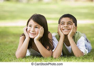 Zwei junge Kinder im Freien liegen im Park lächelnd (wählter Fokus)