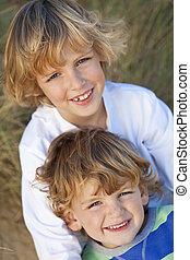 Zwei kleine Jungs, Brüder, zusammen an einem sonnigen Strand
