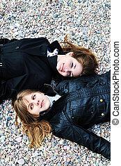 Zwei Teenie-Mädchen liegen auf dem Kiesel