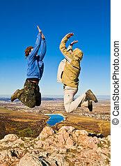 Zwei Wanderer hüpfen fröhlich auf dem Berggipfel